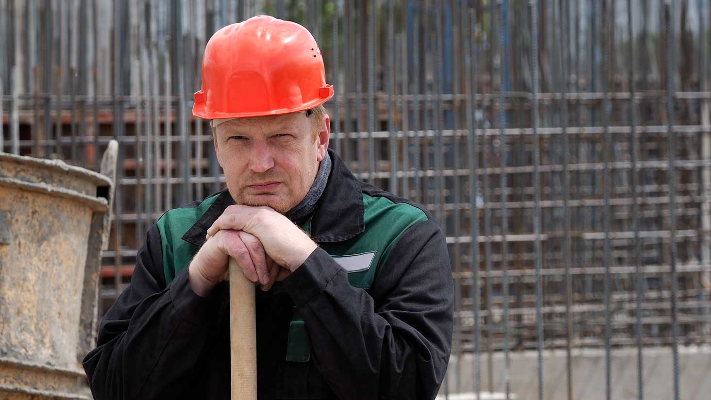 A disgruntled construction worker leaning on his shovel and scowling at the camera.